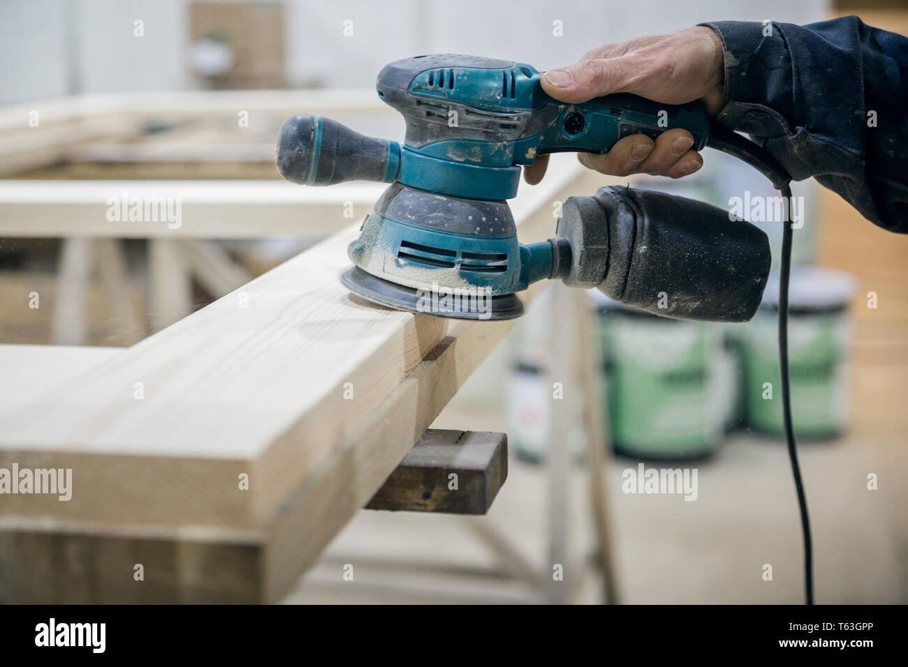 Worker sanding the wooden surface. In the hand of the power tool - Stock Image