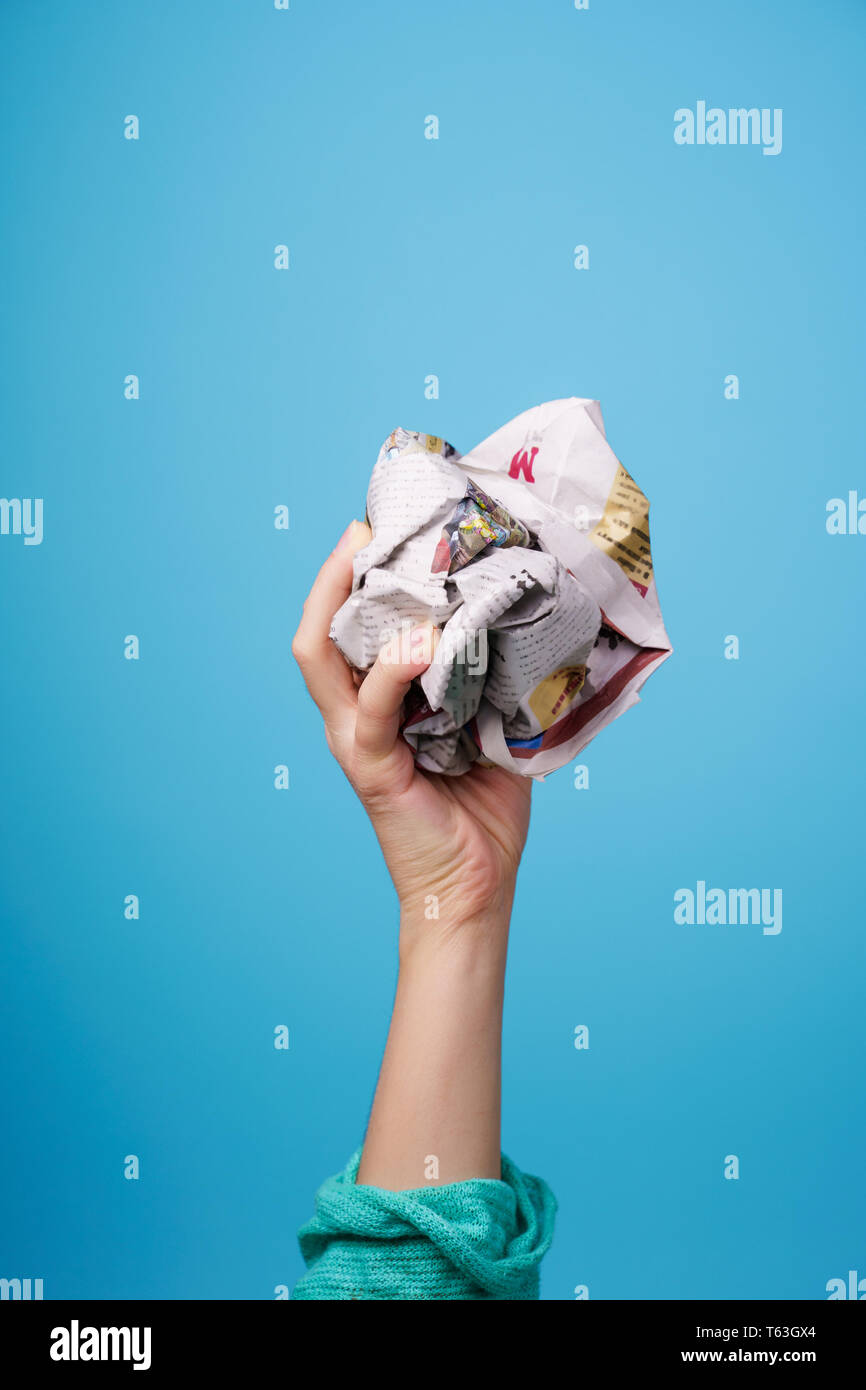 hand with crumpled newspaper on blue background - Stock Image
