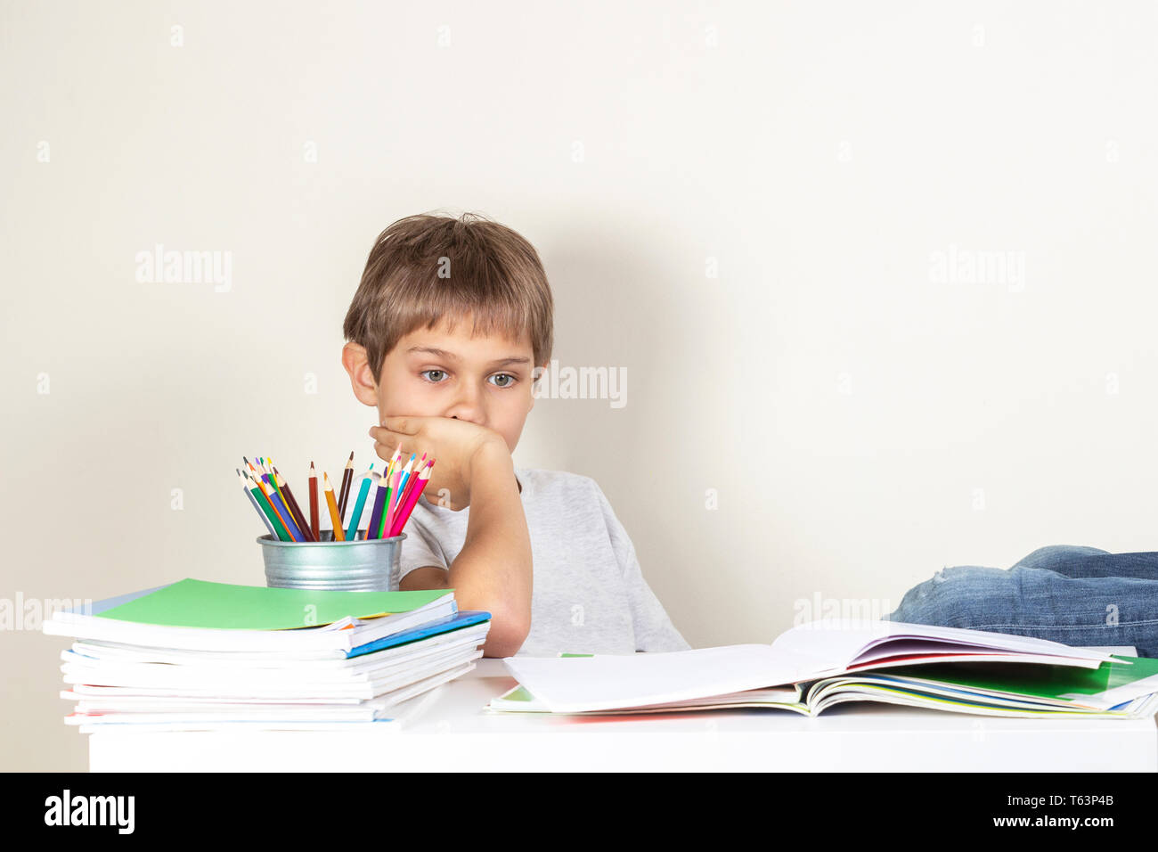 Sad tired child doing homework at the table and thinking - Stock Image
