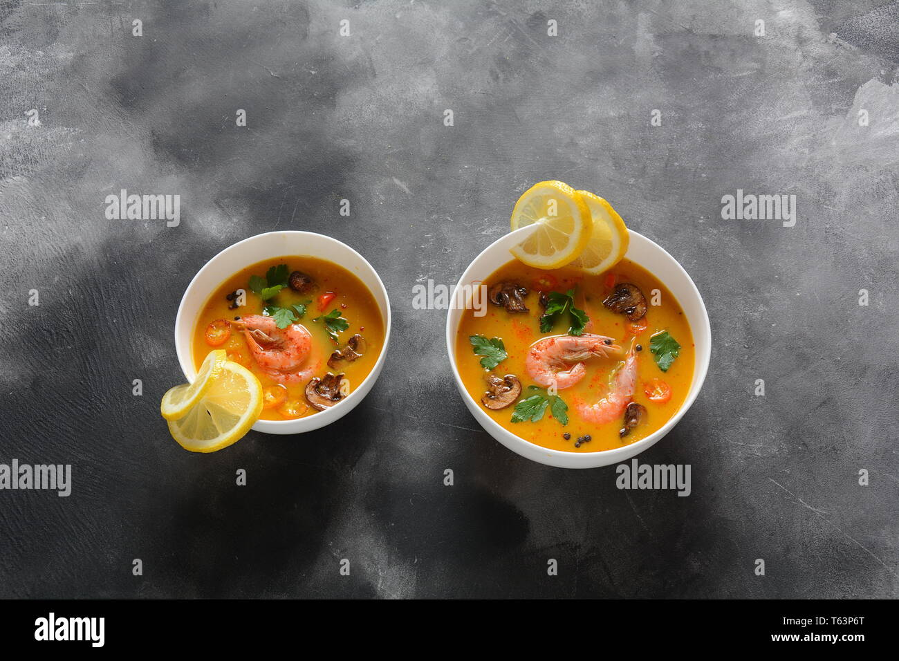 Tom Yum -traditional spicy Thai soup with coconut milk, chili pepper, lemon, mushrooms. Asian soup - Stock Image