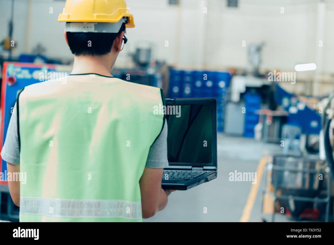 Asian male Industrial engineer in hardhat works with laptop in safety jacket at heavy industry factory. Processing plastic injection molding industry - Stock Image