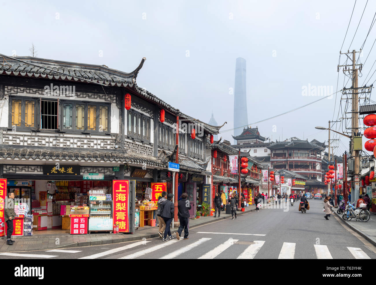Traditional shops and restaurants on Middle Fangbang Road with the Shanghai Tower, just visible through the air pollution, Old Town, Shanghai, China - Stock Image