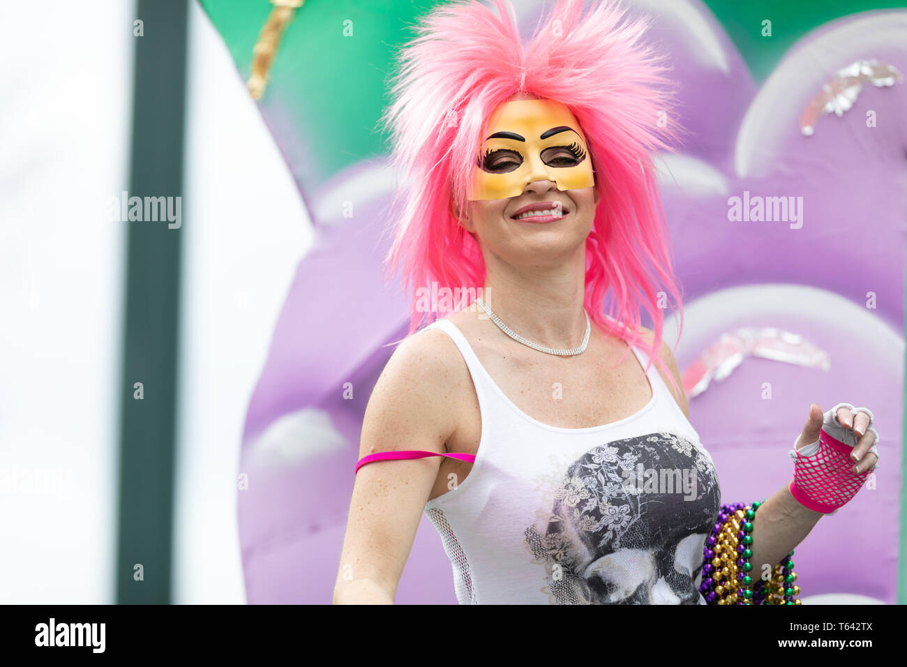 New Orleans, Louisiana, USA - February 23, 2019: Mardi Gras Parade, Woman wearing a pink wig and a face mask, smiling and holding beads necklace on he - Stock Image