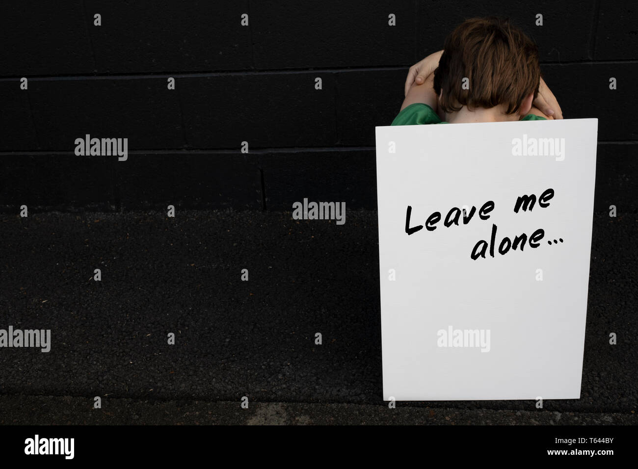 A boy holding a sign, expressing his feelings - Stock Image