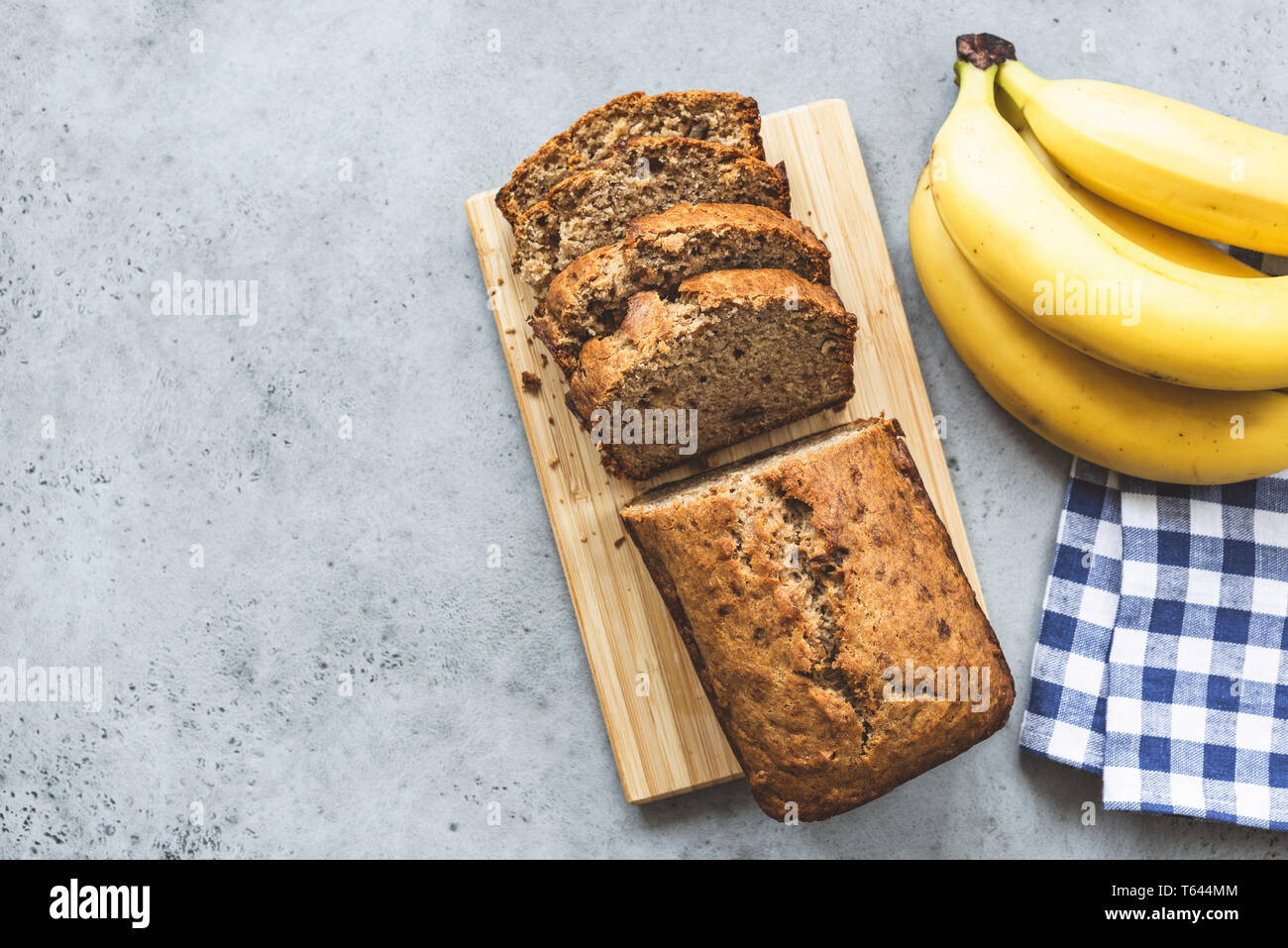 Banana bread loaf with almond nuts sliced on grey concrete background. Table top view and copy space Stock Photo