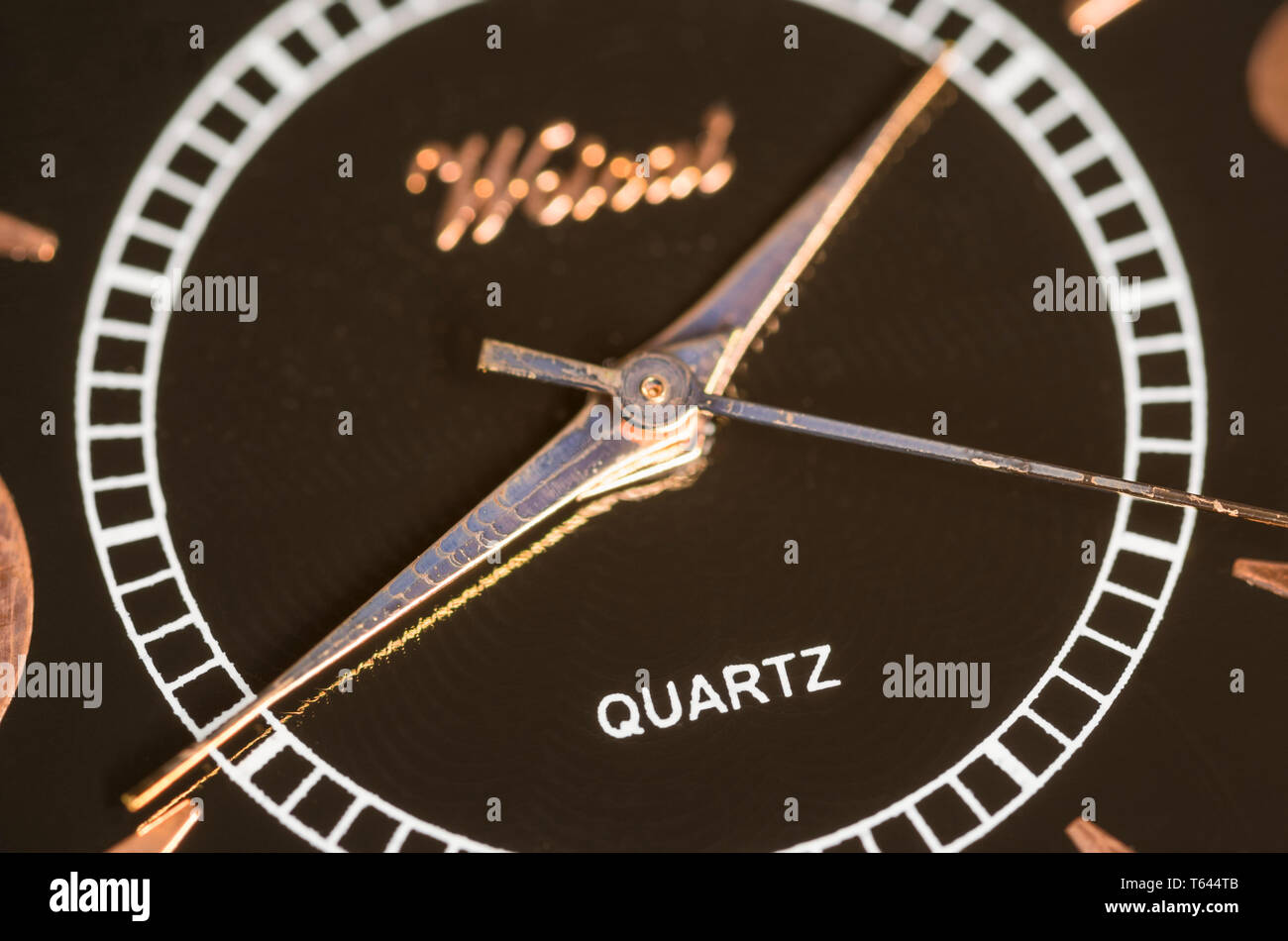 Quartz logo on a watch or clock face using a quartz mechanism showing hour, minute and second hands. - Stock Image