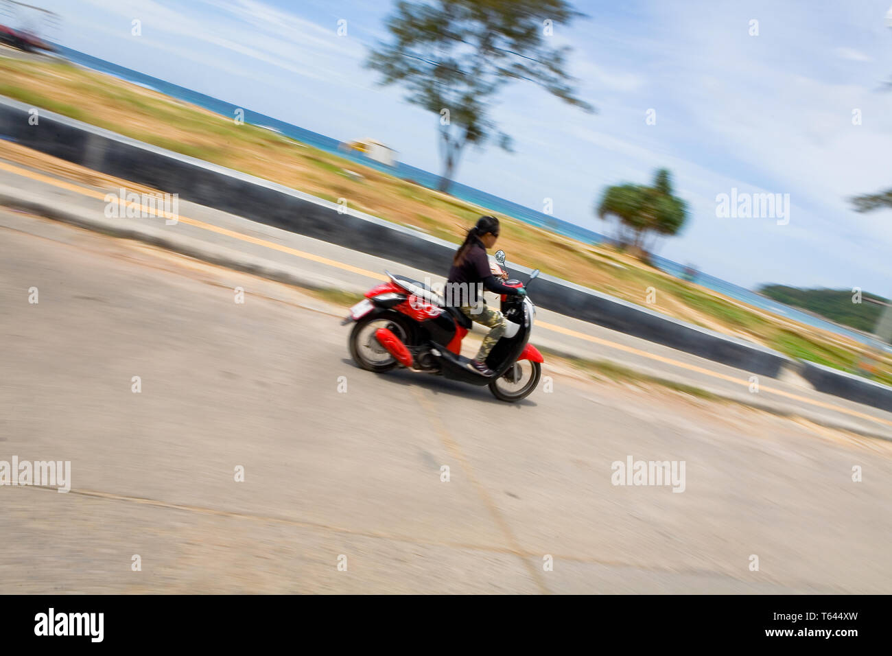 Karon, Thailand, February 20, 2018: East Asian woman riding at high speed on a scooter along the promenade. Dynamics and speed. - Stock Image