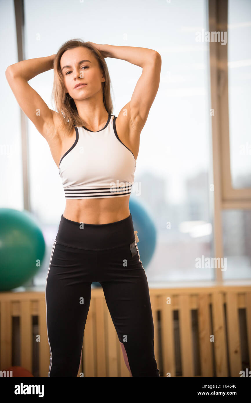 Young athletic blonde woman standing in the fitness studio Stock Photo