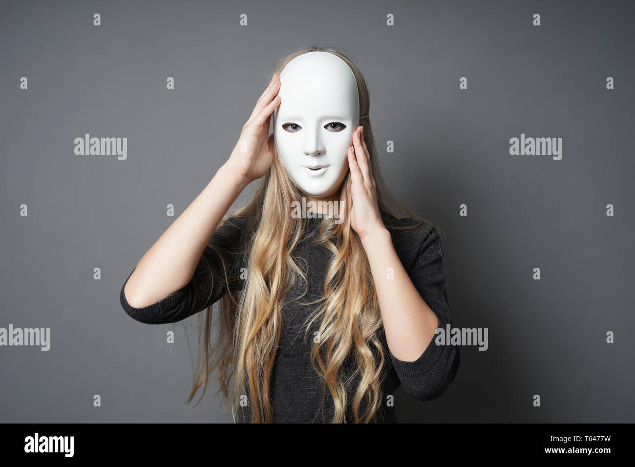 mysterious young woman adjusting her mask with her hands - Stock Image