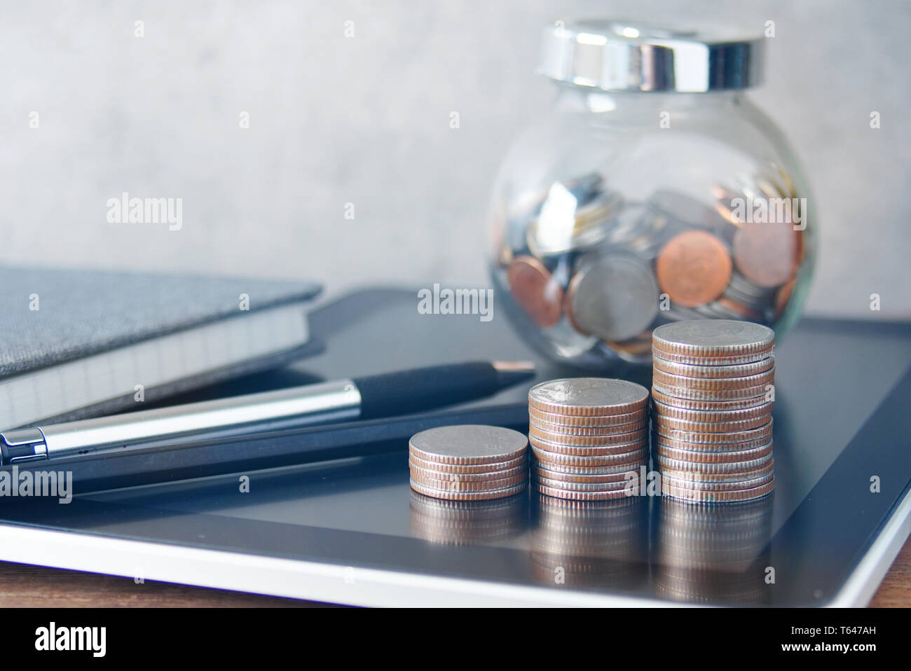 Growth shape coins stack and pen and glass cup carry coins lay on tablet on the table,financial concept. - Stock Image