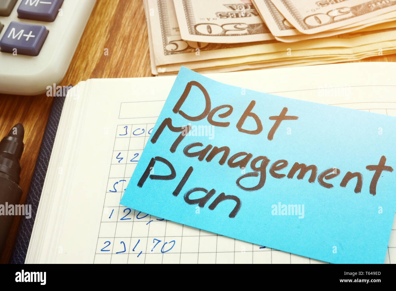Debt management plan with calculator and cash. - Stock Image