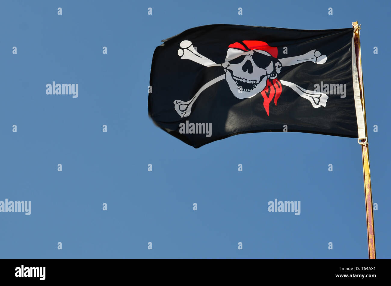 ff862e89 Pirate flag against clear, blue sky fluttering in the wind, copy space -  Stock