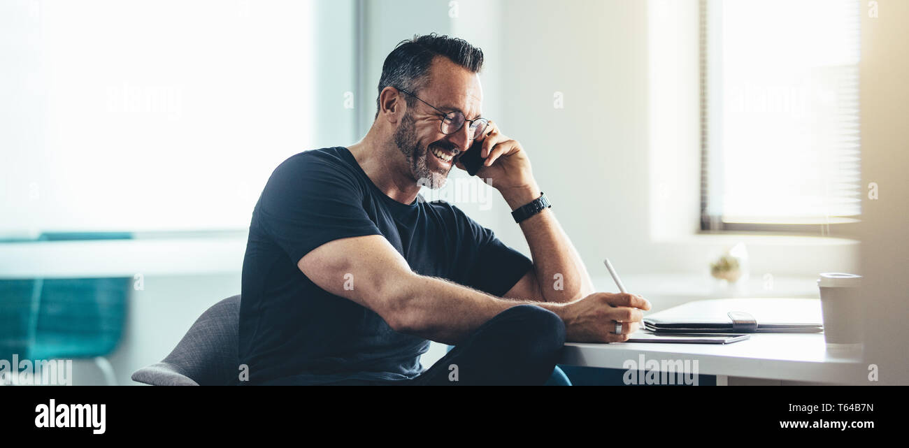 Smiling man at work talking on cell phone and working on his digital tablet. Cheerful businessman working in office. Stock Photo