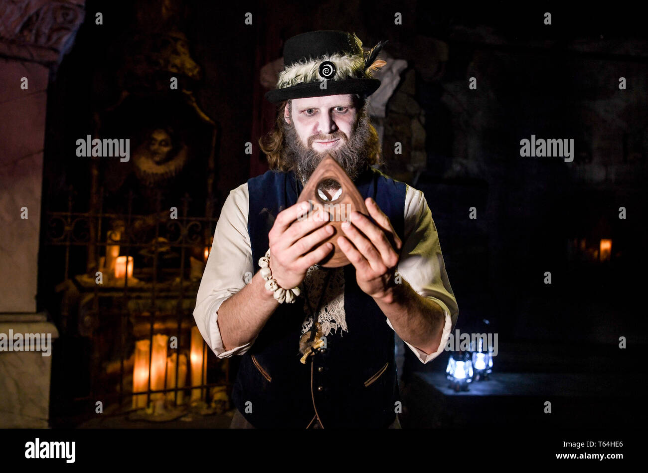 Berlin, Germany. 24th Apr, 2019. The actor Alex van Ric (as medium) with an Ouija. The show 'Séance - Do you feel her too?' is about a medium that tries to conjure up the spirit of a woman during a necromancy. Credit: Britta Pedersen/dpa-Zentralbild/ZB/dpa/Alamy Live News - Stock Image