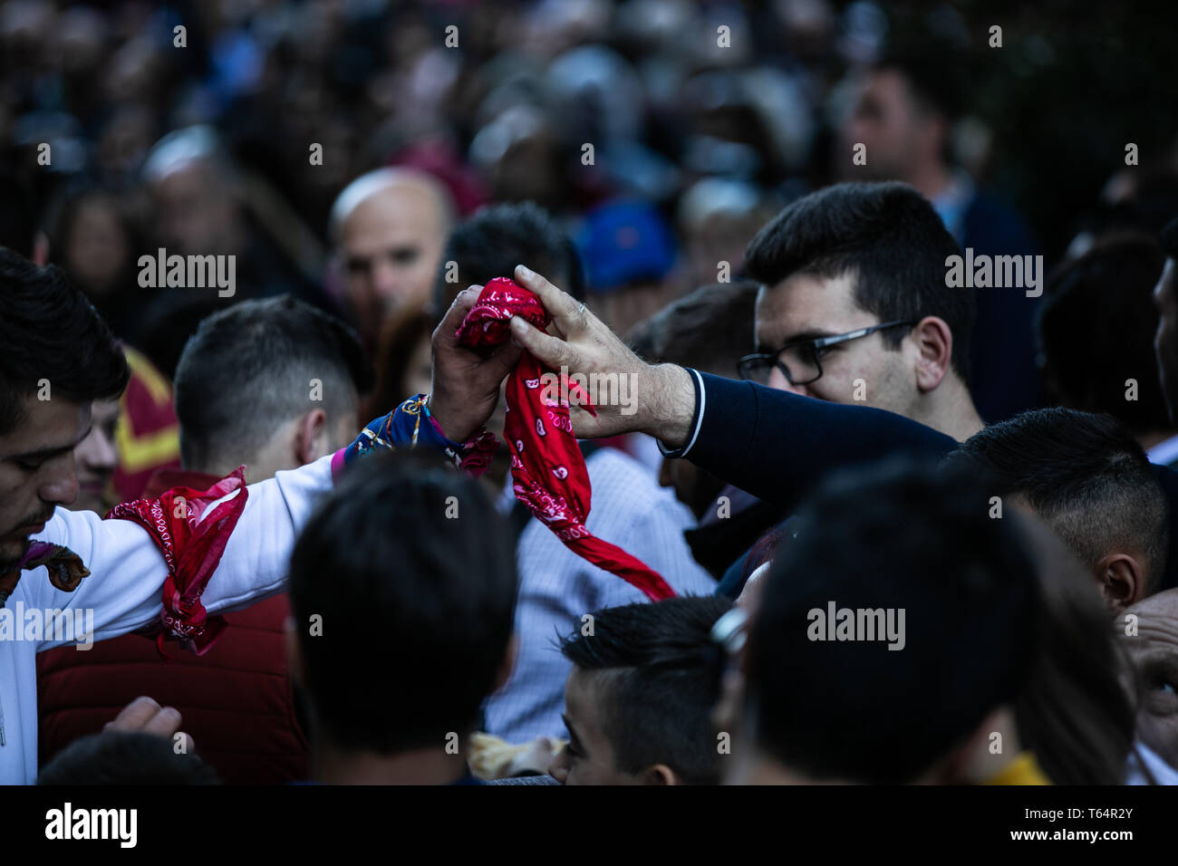 Meteora, Greece. 29th Apr, 2019. Villagers hand each other scarves at Meteora complex of sandstone cliffs in Kastraki village, central Greece, on April 29, 2019. Following a 300-year traditional custom during the annual celebrations of Saint George's Day, climbers hang colorful scarves near an old ruined monastery built in a cave 40 meters above the village on the sandstone rocks and return with the old ones, which can be given away as a token of good health. Credit: Lefteris Partsalis/Xinhua/Alamy Live News - Stock Image