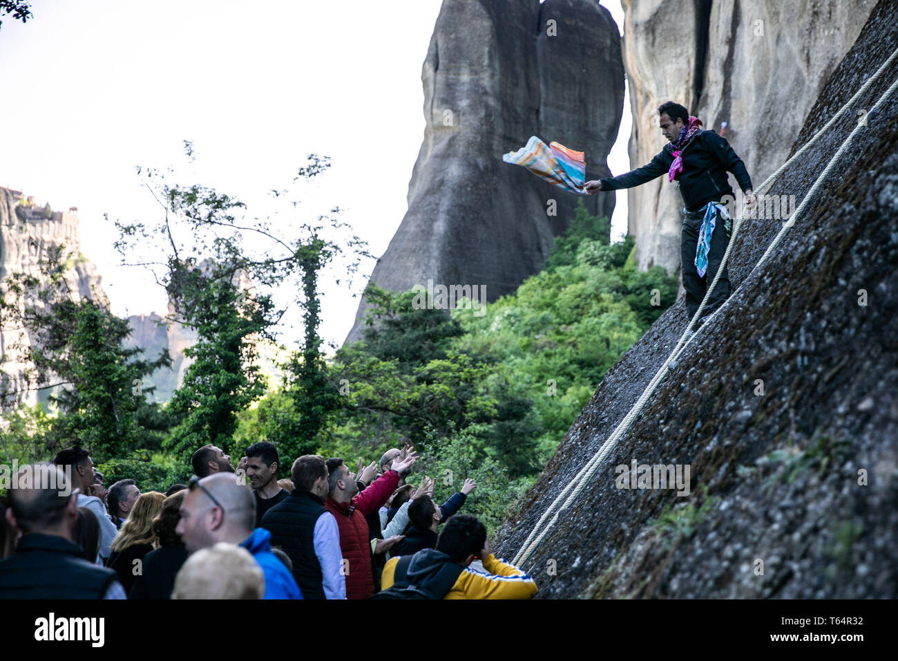 Meteora, Greece. 29th Apr, 2019. A climber gives away scarves at Meteora complex of sandstone cliffs in Kastraki village, central Greece, on April 29, 2019. Following a 300-year traditional custom during the annual celebrations of Saint George's Day, climbers hang colorful scarves near an old ruined monastery built in a cave 40 meters above the village on the sandstone rocks and return with the old ones, which can be given away as a token of good health. Credit: Lefteris Partsalis/Xinhua/Alamy Live News - Stock Image