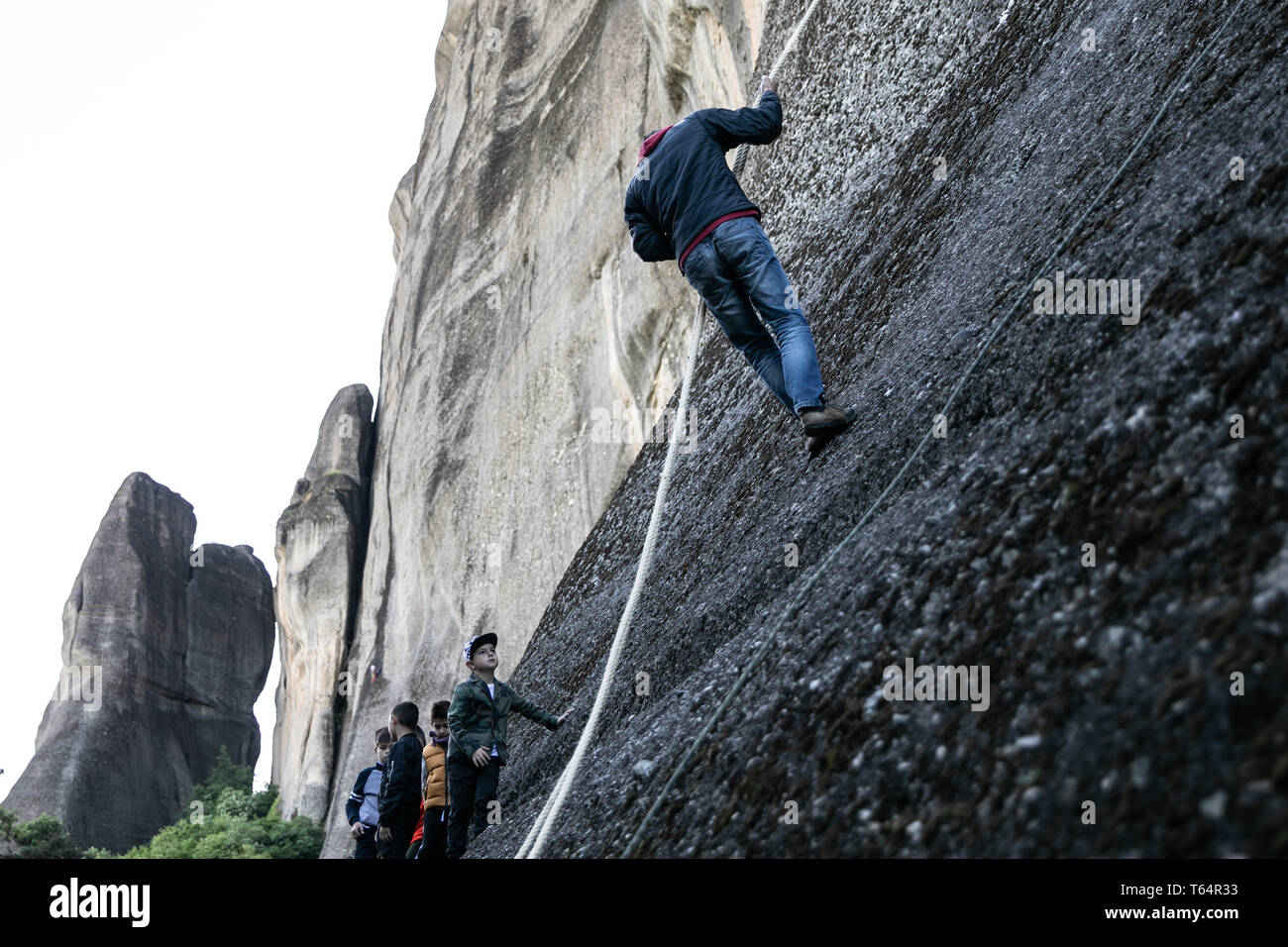 Meteora, Greece. 29th Apr, 2019. A climber climbs up Meteora complex of sandstone cliffs in Kastraki village, central Greece, on April 29, 2019. Following a 300-year traditional custom during the annual celebrations of Saint George's Day, climbers hang colorful scarves near an old ruined monastery built in a cave 40 meters above the village on the sandstone rocks and return with the old ones, which can be given away as a token of good health. Credit: Lefteris Partsalis/Xinhua/Alamy Live News - Stock Image