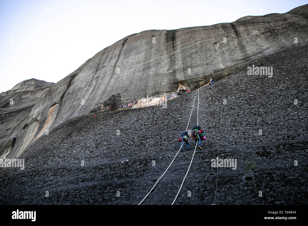 Meteora, Greece. 29th Apr, 2019. Climbers climb up Meteora complex of sandstone cliffs in Kastraki village, central Greece, on April 29, 2019. Following a 300-year traditional custom during the annual celebrations of Saint George's Day, climbers hang colorful scarves near an old ruined monastery built in a cave 40 meters above the village on the sandstone rocks and return with the old ones, which can be given away as a token of good health. Credit: Lefteris Partsalis/Xinhua/Alamy Live News - Stock Image