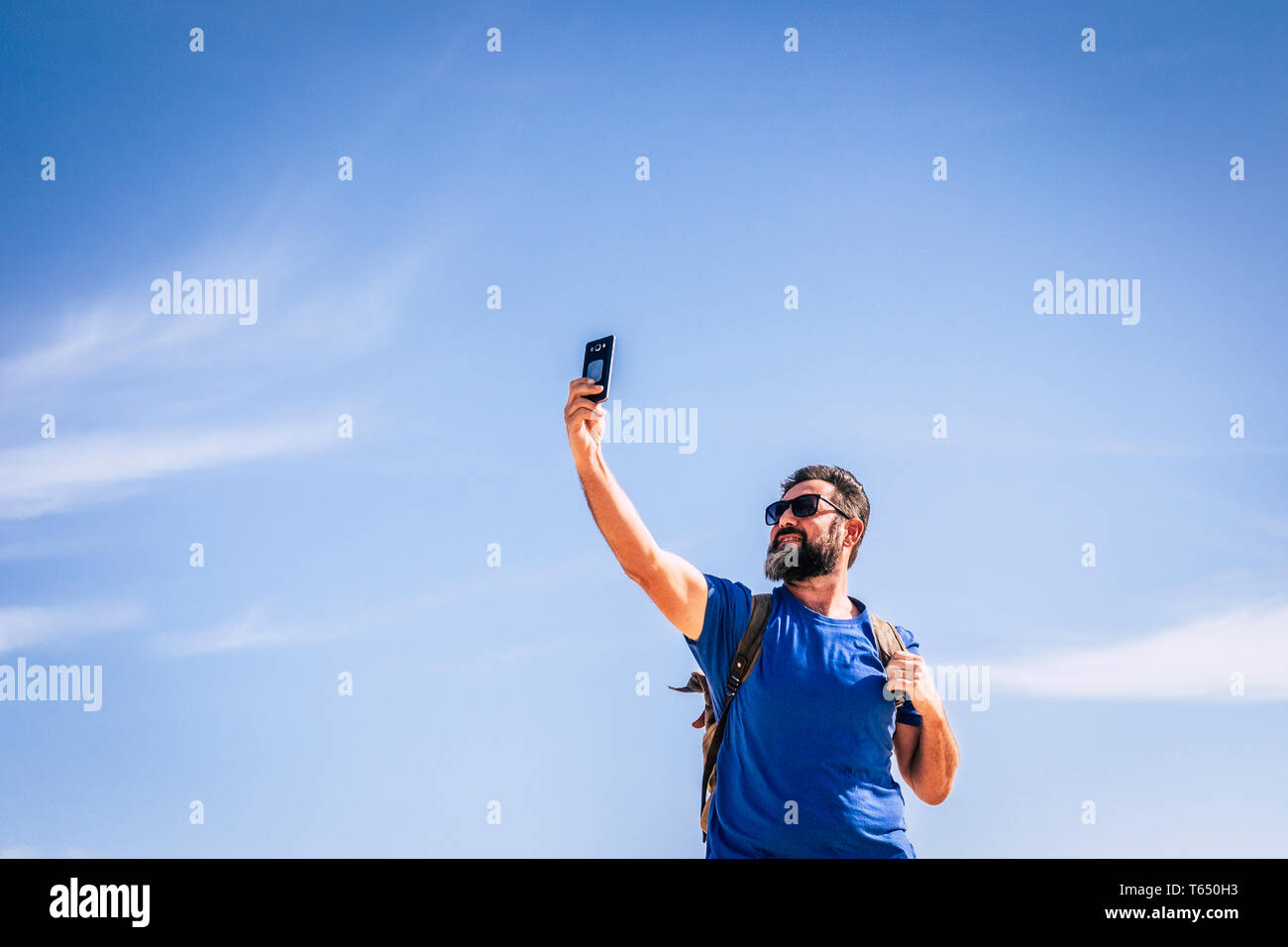 People and internet technology man with beard and sunlgasses loooking for signal with a mobile phone device - people traveling with backpack for adven Stock Photo