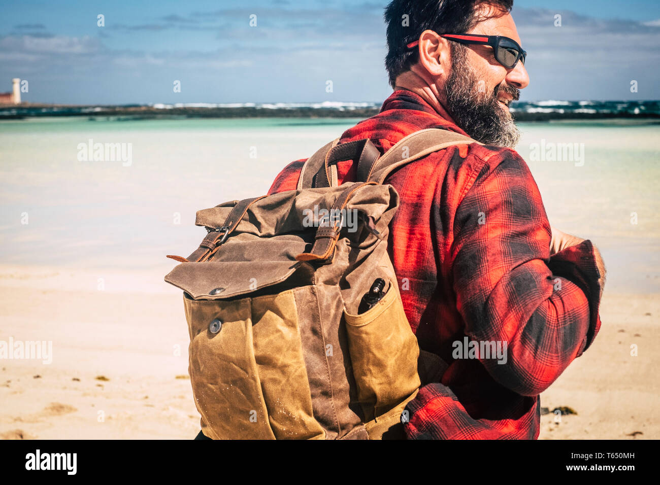 Travel and backpack wanderlust concept people with adult hipster man with beard and sunglasses enjoying the outdoor leisure activity with beach and be Stock Photo
