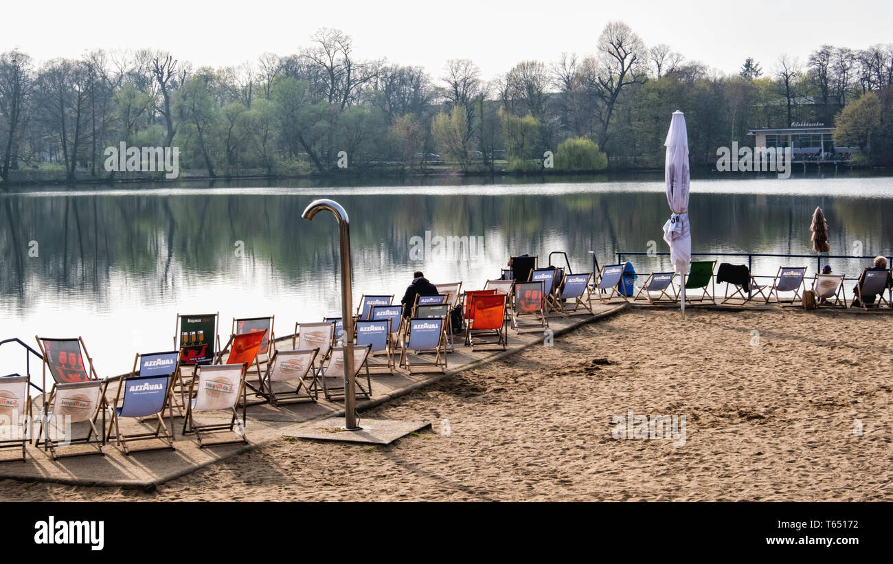 Berlin,Pankow. Weissensee Strandbad, White Lake bathing beach with deck chairs and sunshades. Wild water swimming site. - Stock Image