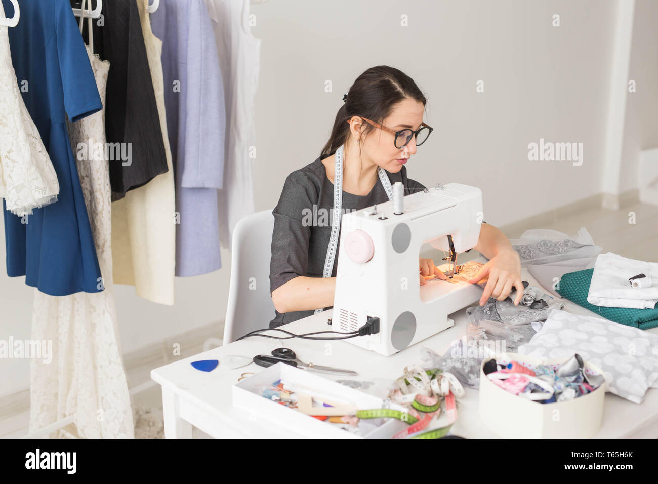 Dressmaker Tailor Works And Seamstress Concept High Angle View Portrait Of Smiling Fashion Designer In Glasses Using Sewing Machine Stock Photo Alamy
