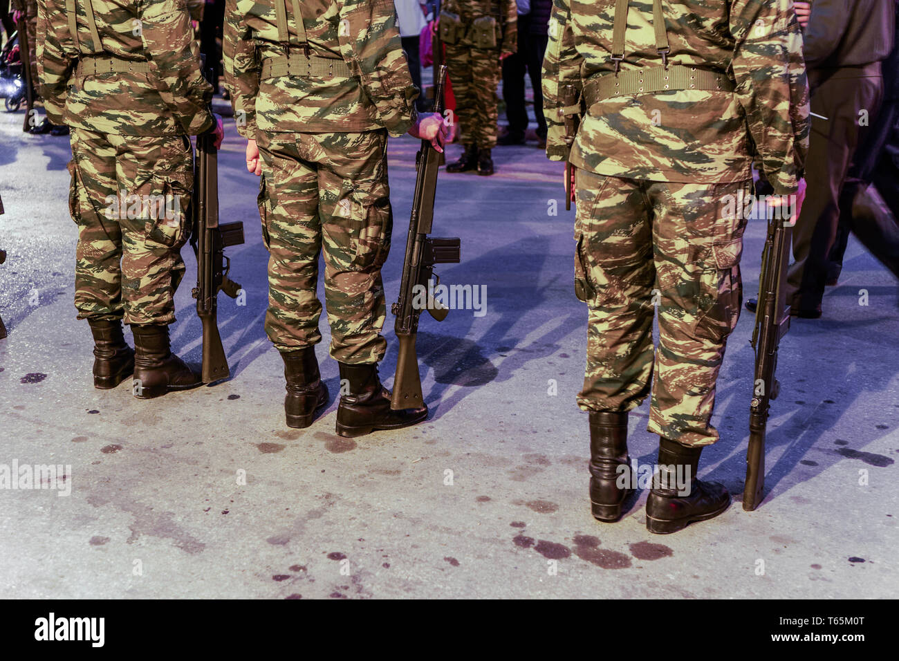 Silhouette of Hellenic Armed forces males standing still. Greek Army soldiers in a Camouflage Pattern combat uniform, holding a G3A4 rifle. - Stock Image