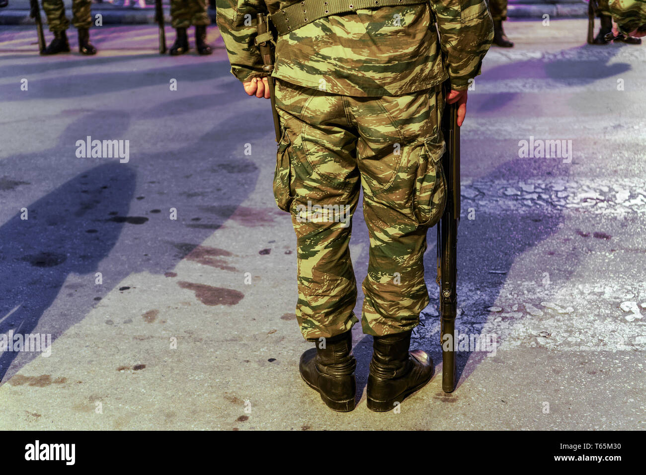Silhouette of Hellenic Armed forces male standing still. Greek Army soldier in a Camouflage Pattern combat uniform, holding a G3A4 rifle. - Stock Image