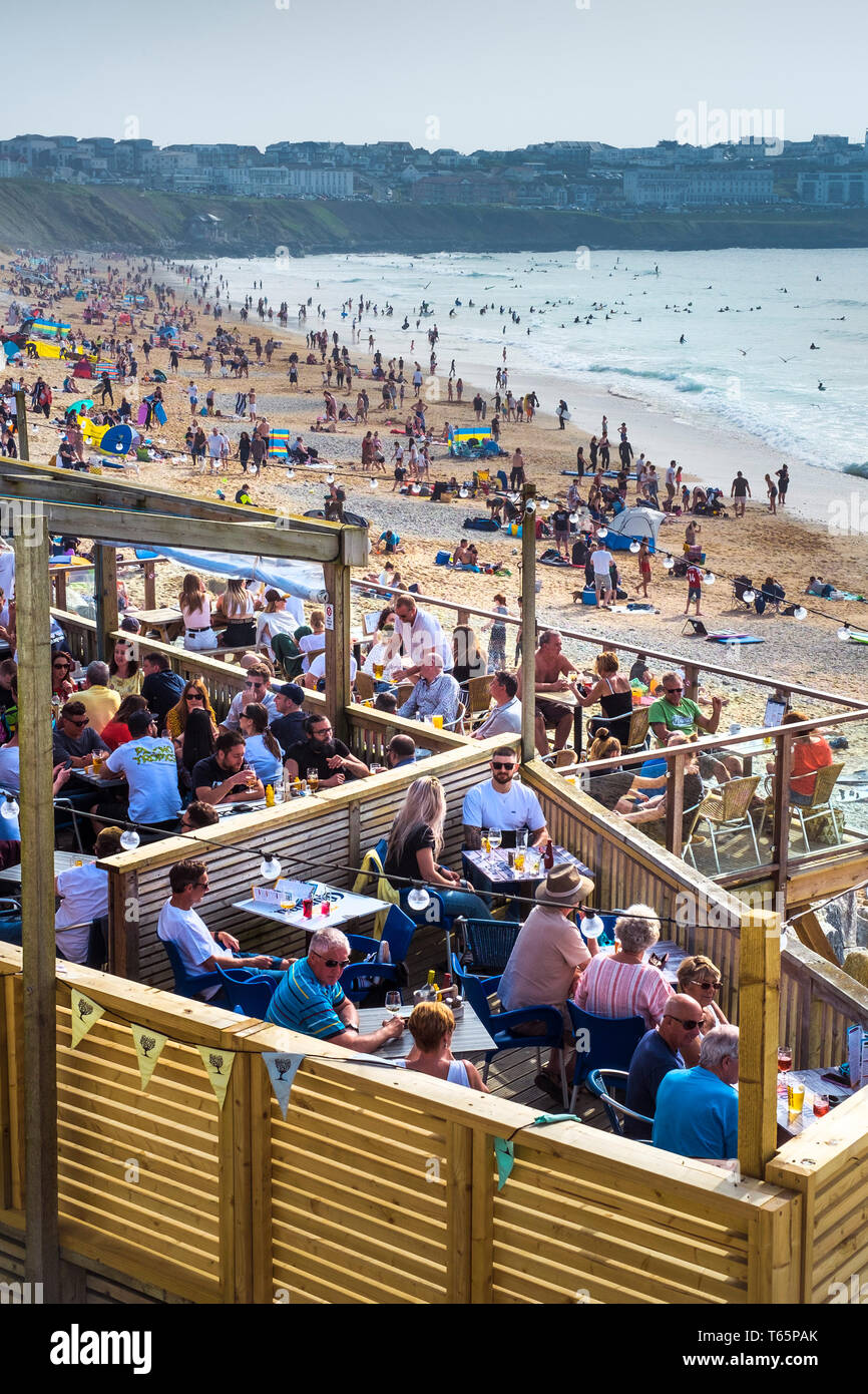 Holidaymakers enjoying the sunshine at a busy Fistral Beach in Newquay in Cornwall. - Stock Image