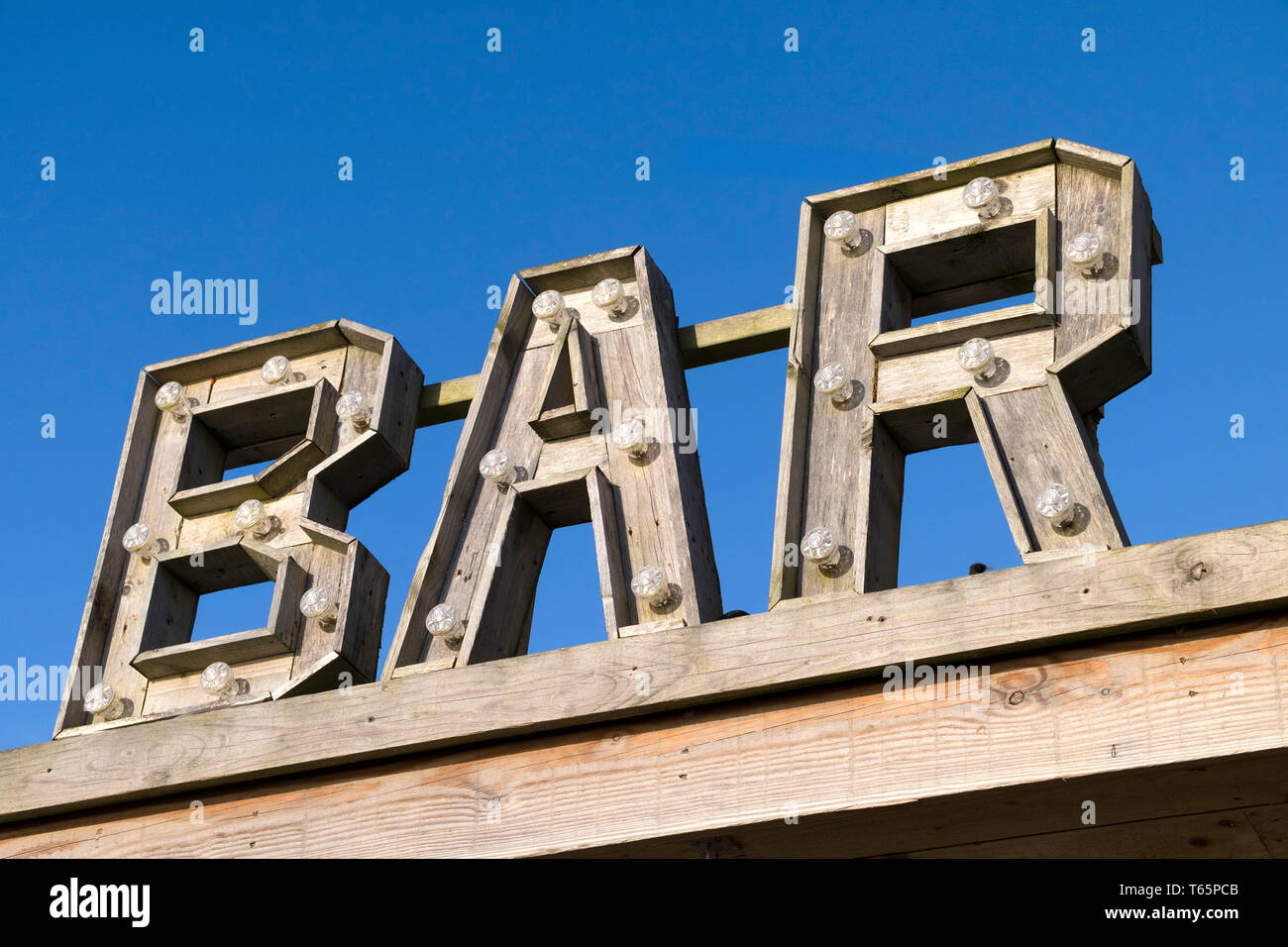 A wooden sign for the Bar at Fistral in Newquay in Cornwall. - Stock Image