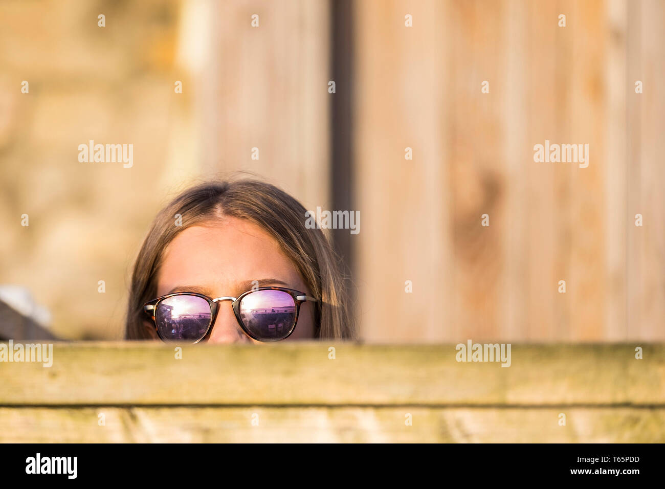 A holidaymaker wearing sunglass peeking over a wooden fence. - Stock Image