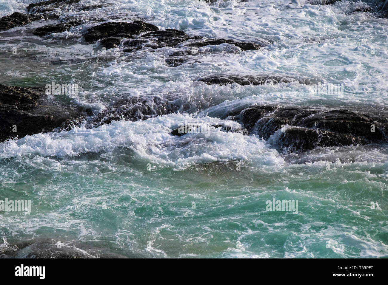 Sea swirling around and over rocks on the North Cornwall coast. - Stock Image