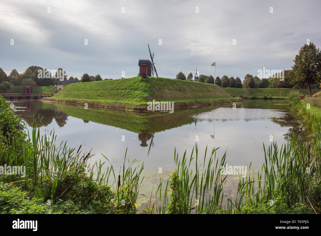 Looking at the fortified wall of Bourtange with the windmill in the background - Stock Image