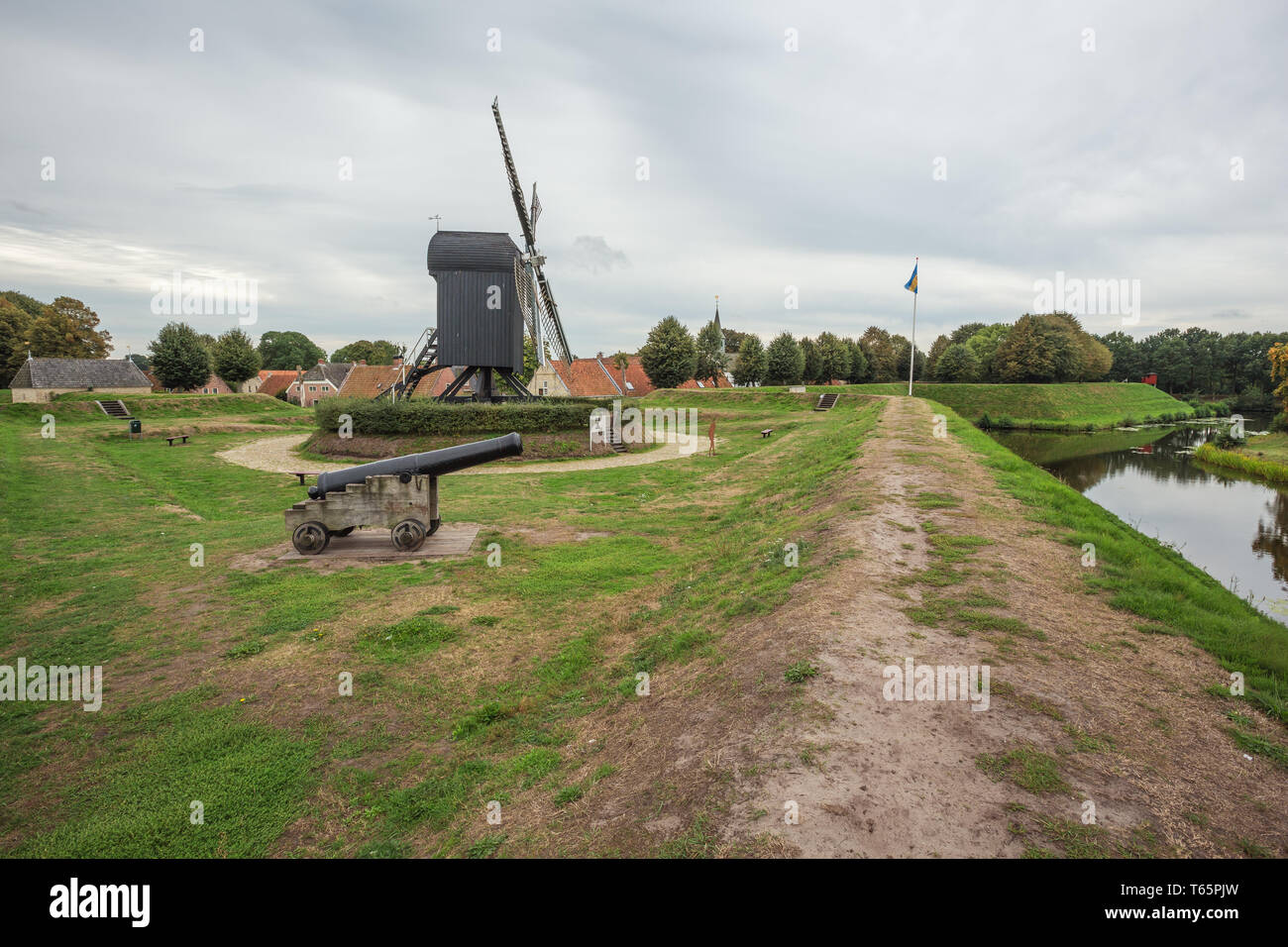 On top of the wall of Bourtange with the windmill and an old cannon - Stock Image