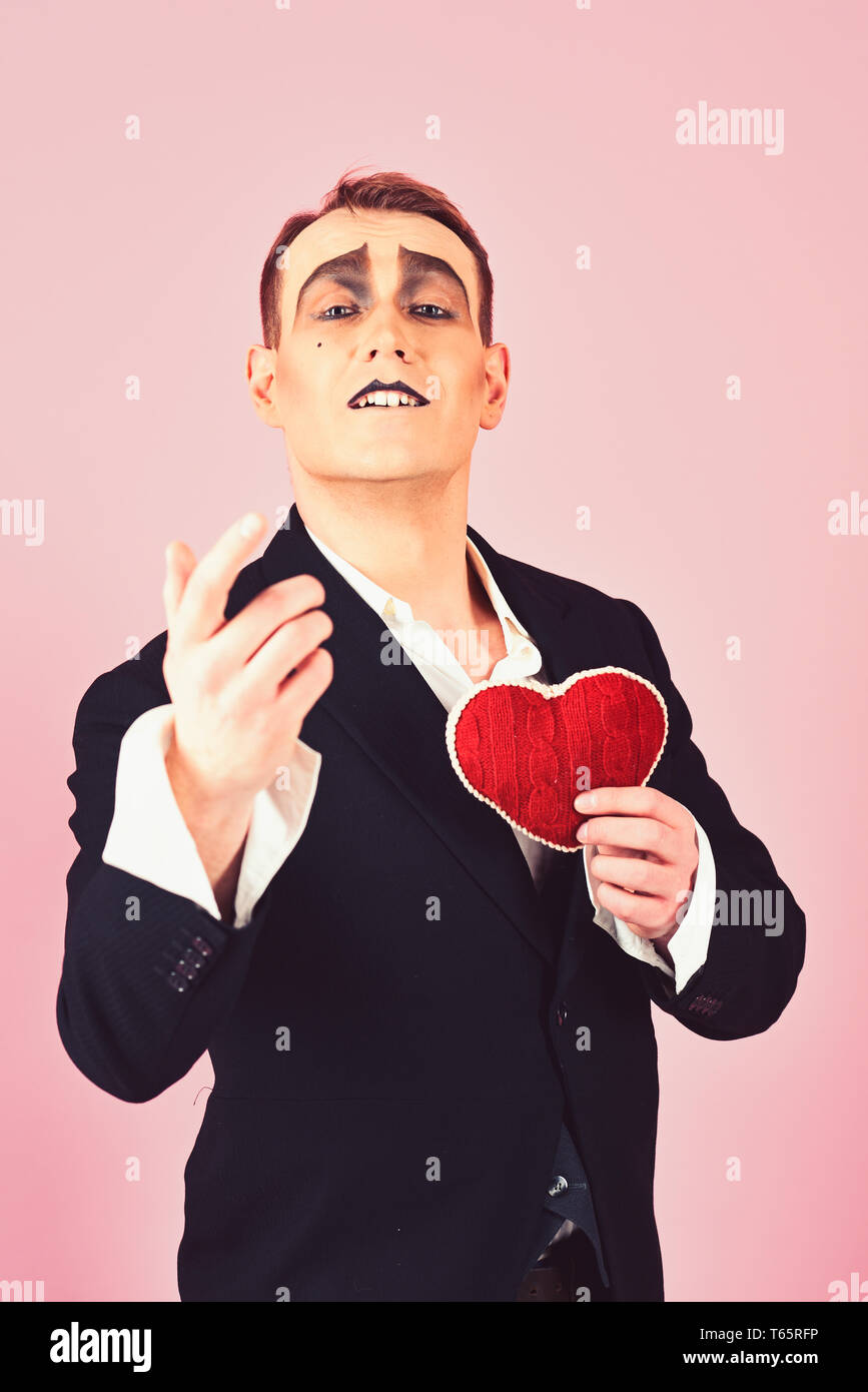 Performing love on stage. Theatre actor pantomime falling in love. Mime man hold red heart for valentines day. Mime actor with love symbol. Love - Stock Image