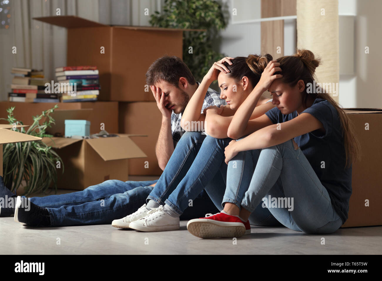 Three sad evicted roommates moving home complaining sitting on the floor - Stock Image