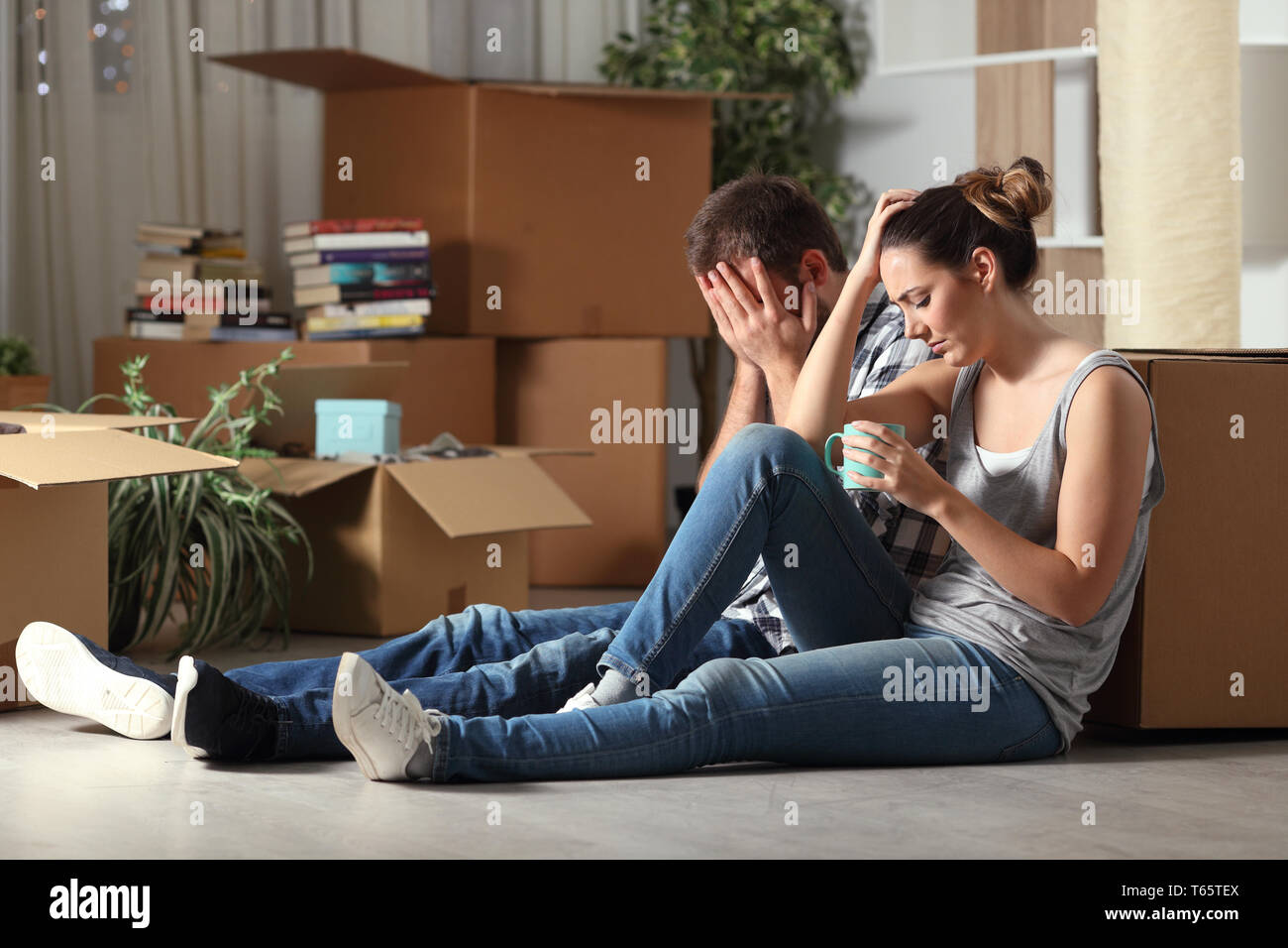 Sad evicted couple moving home complaining sitting on the floor in the night - Stock Image