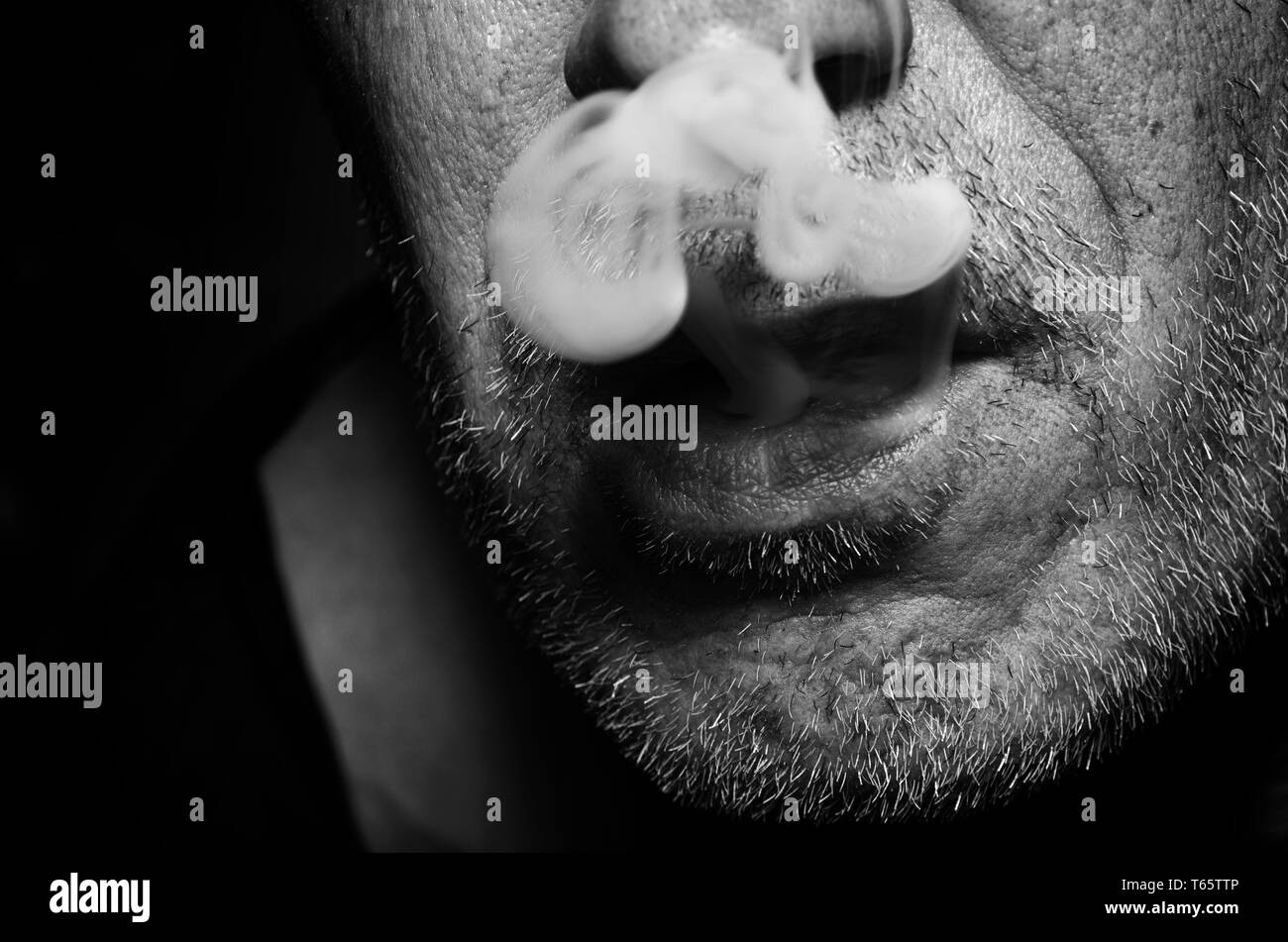Smoking man releases smoke from mouth to black and white. - Stock Image
