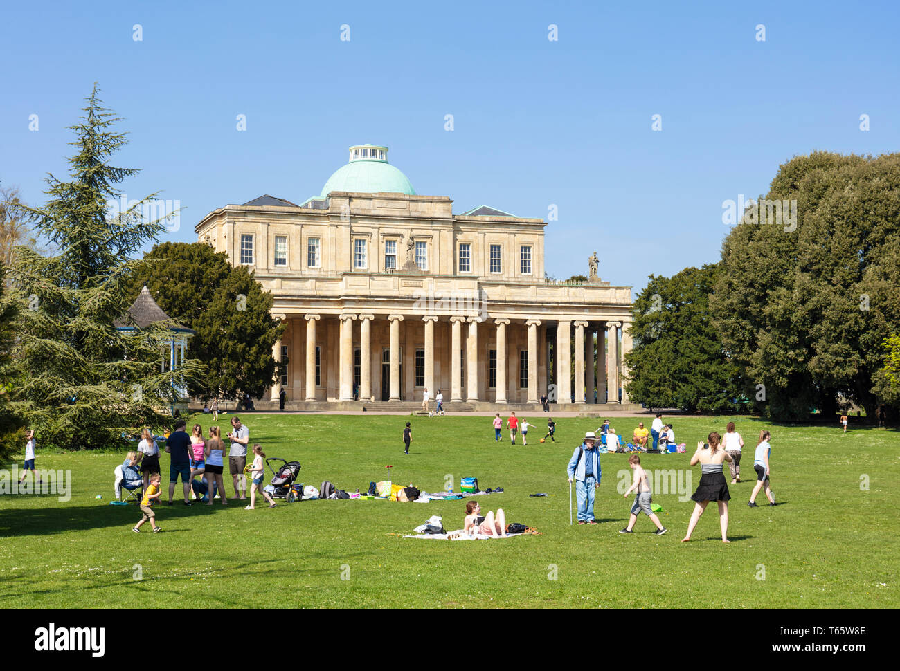 Cheltenham Pittville Pump Room with people having a picnic and children playing Pittville Park, Cheltenham Spa Gloucestershire, England, UK,GB, Europe - Stock Image