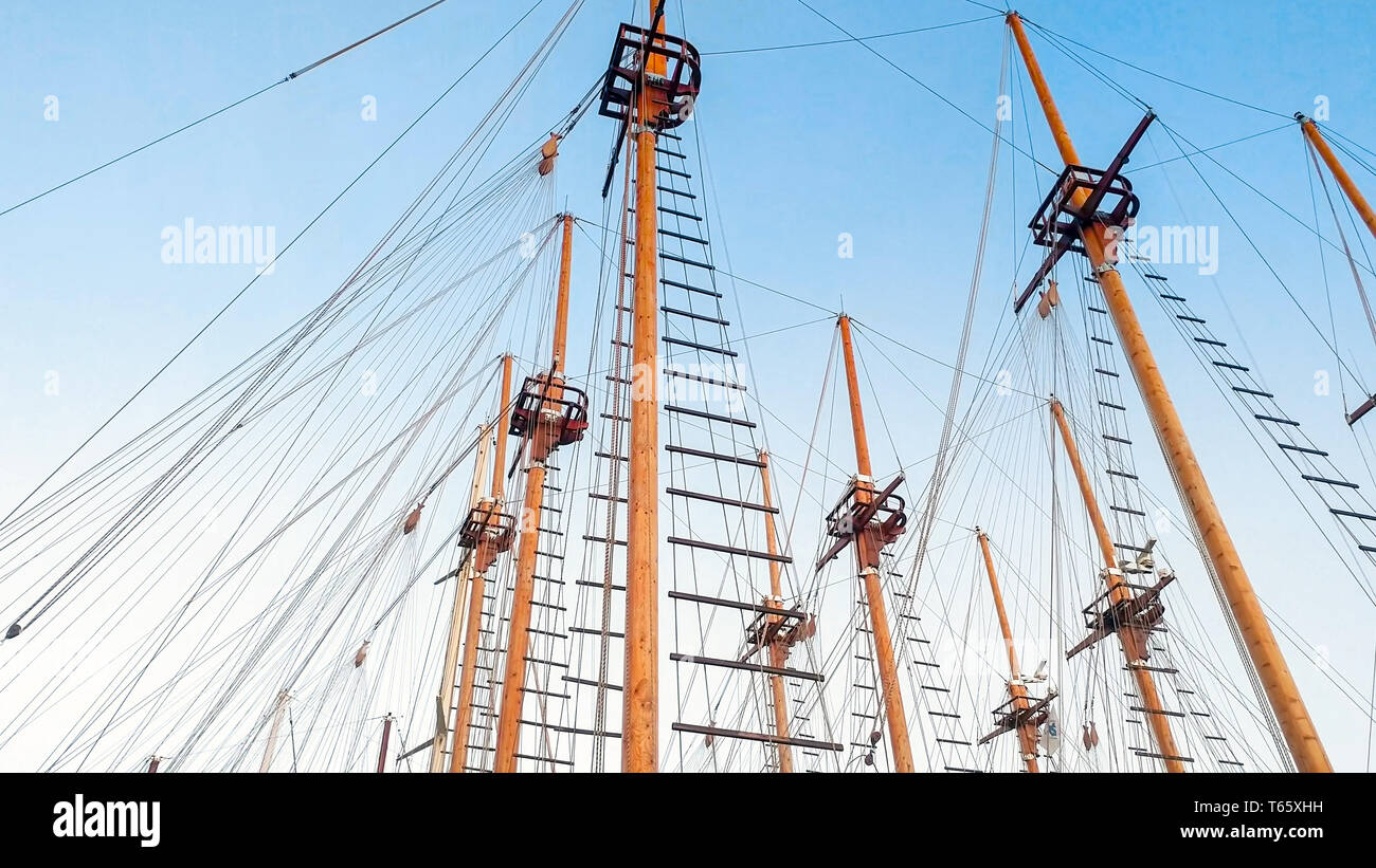 Lots of wooden masts of historic ships against blue sky - Stock Image