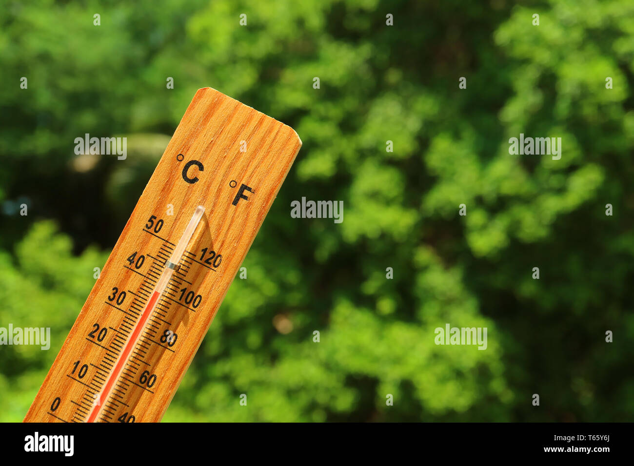 Wooden thermometer in the summer sunlight showing high temperature - Stock Image