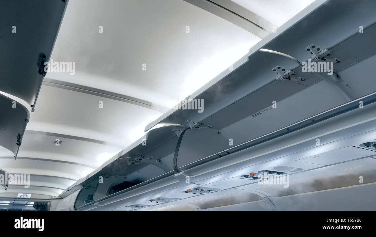 Cold steam flowing from under the ceiling of passenger airplane - Stock Image
