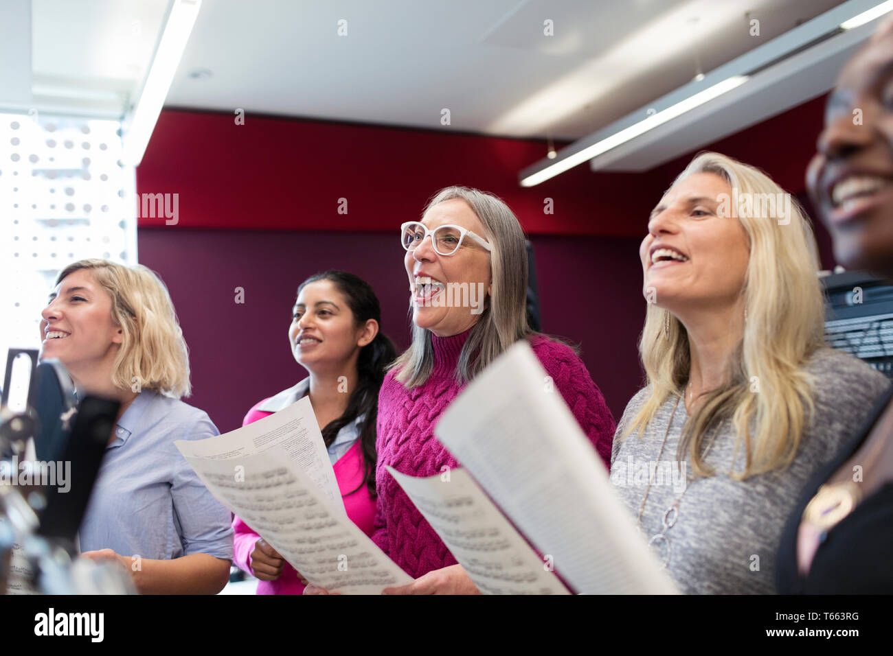Womens choir with sheet music singing in music recording studio - Stock Image