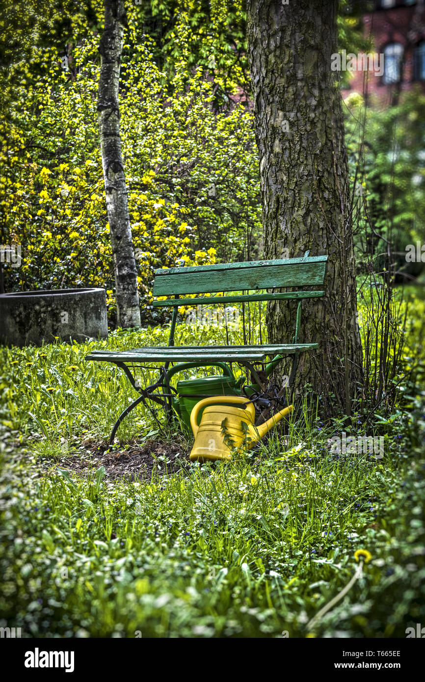 garden bench with yellow ewer Stock Photo
