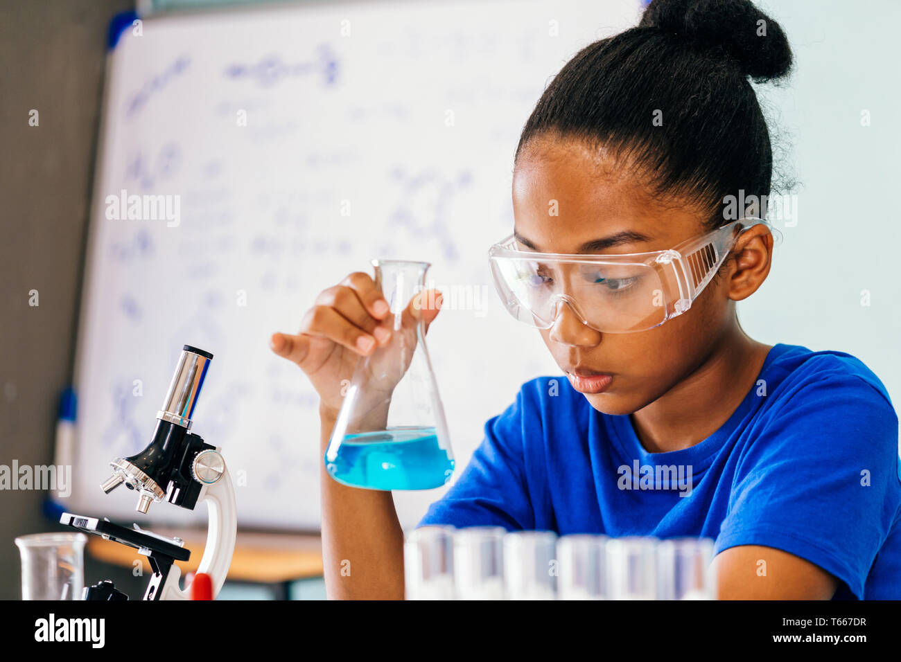 Young African American Mixed Kid Testing Chemistry Lab Experiment And Shaking Glass Tube Flask Along With