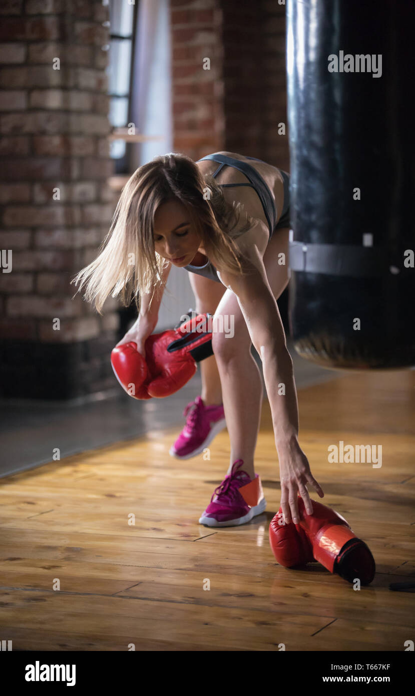 A woman boxer puts up boxer gloves from the floor and putting it on - Stock Image