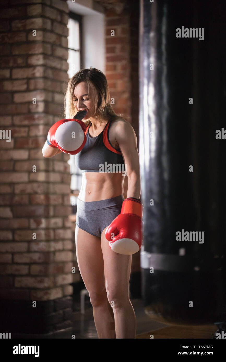 An athletic woman in boxers gloves standing near the punching bag Stock Photo