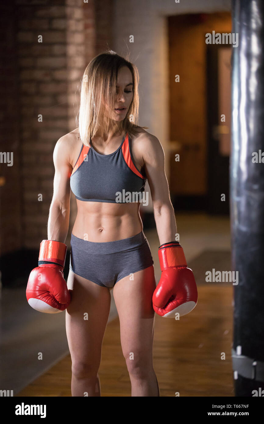 An athletic woman in boxers gloves standing in the gym and posing for the camera - Stock Image