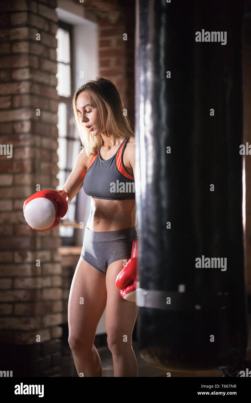An athletic woman in boxers gloves standing near the punching bag in the gym Stock Photo