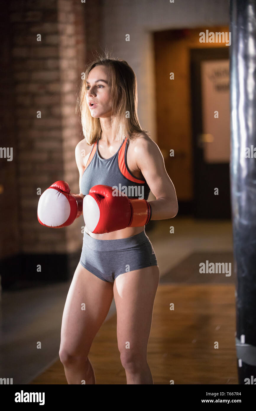 An athletic woman in boxers gloves standing in the bright gym on the training Stock Photo